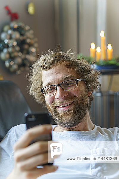 Portrait of happy man with smartphone at home at Christmas time