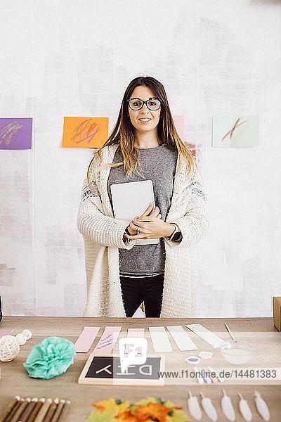Porträt einer lächelnden jungen Frau  die mit handgemachten Dingen am Schreibtisch steht