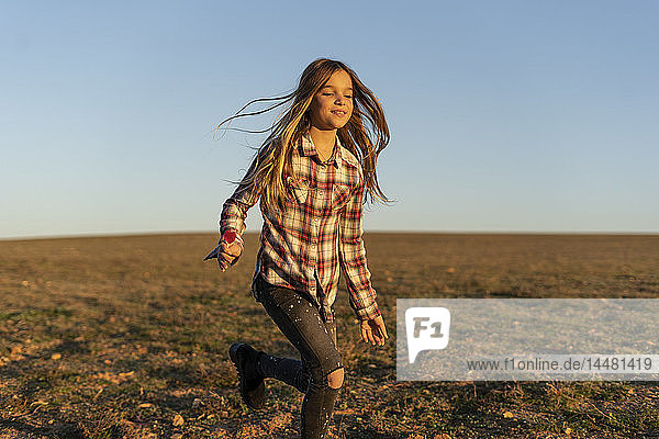 Portrait of smiling girl with lollipop running on pasture by sunset