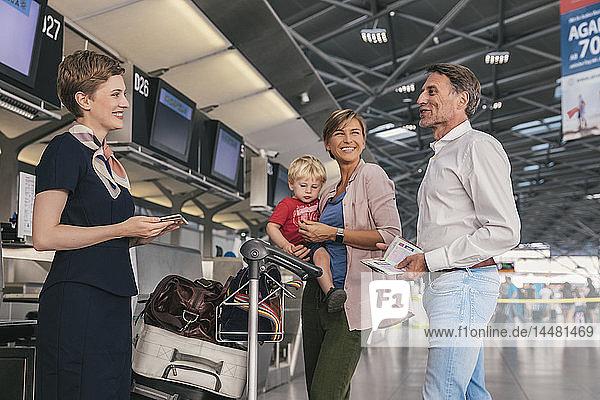 Glückliche Familie mit Airline-Mitarbeiter beim Check-in am Flughafen