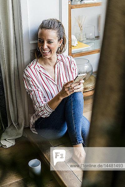 Lachende Frau sitzt zu Hause mit Handy auf dem Boden