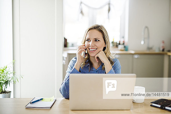 Lächelnde Frau mit Laptop und Handy bei der Arbeit zu Hause