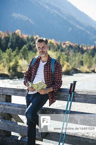 Österreich  Alpen  Mann auf Wanderung mit Karte auf einer Brücke