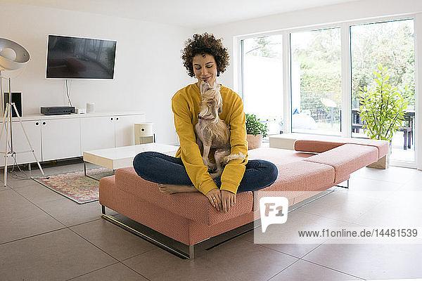 Frau mit Hund sitzt zu Hause auf dem Sofa