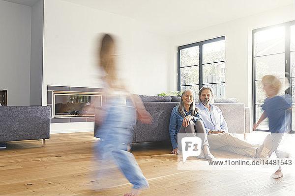 Grandparents observing grandchildren  playing in livingroom