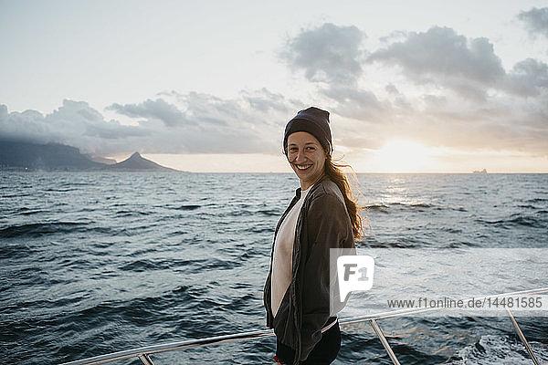 Südafrika  junge Frau mit Wollmütze lächelt während einer Bootsfahrt bei Sonnenuntergang