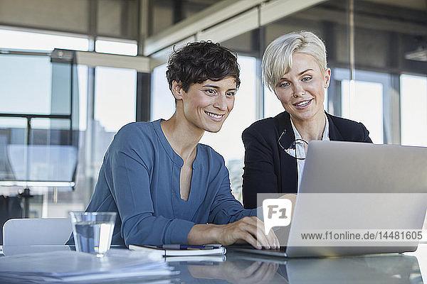Zwei lächelnde Geschäftsfrauen teilen sich den Laptop am Schreibtisch im Büro