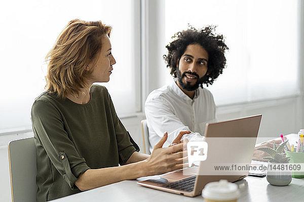 Junge Geschäftsleute im Coworking Space unterstützen sich gegenseitig