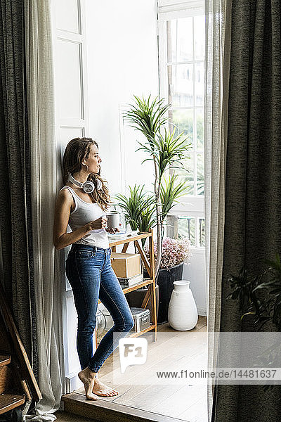 Frau mit Tasse Kaffee und Kopfhörern steht zu Hause im Türrahmen