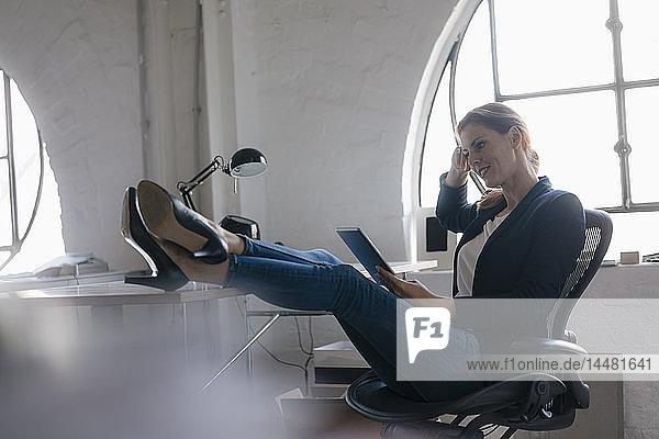 Geschäftsfrau mit Tablett mit Füßen auf Schreibtisch im Büro