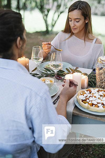 Paar beim romantischen Essen bei Kerzenlicht im Garten