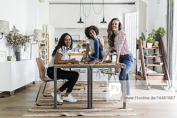 Portrait of three happy women at table at home