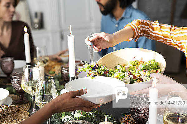 Woman serving salad on a friend's plate at a dinner party