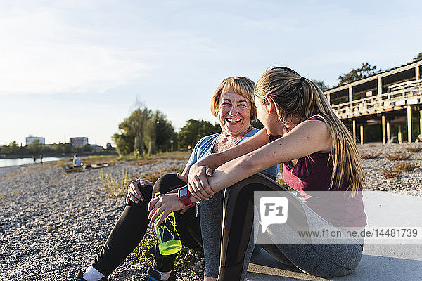 Großmutter und Enkelin machen eine Pause nach dem Training am Fluss