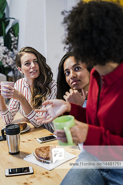 Three women talking at table