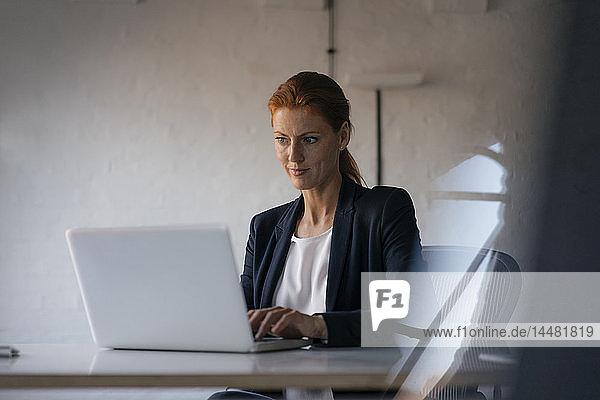 Geschäftsfrau mit Laptop am Schreibtisch im Büro