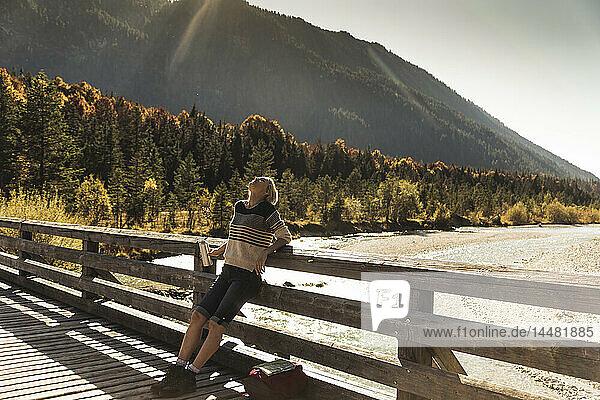 Österreich  Alpen  Frau auf einer Wanderung mit Pause auf einer Brücke