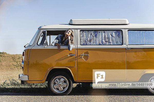 Hübsche Frau auf einer Autoreise mit ihrem Wohnwagen  die aus dem Autofenster schaut