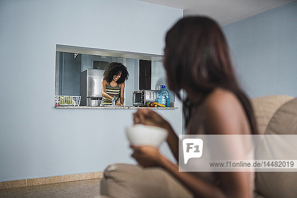 Woman watching her friend working in the kitchen