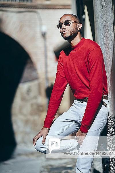 Porträt eines modischen jungen Mannes in rotem Pullover und Socken  der das Sonnenlicht genießt