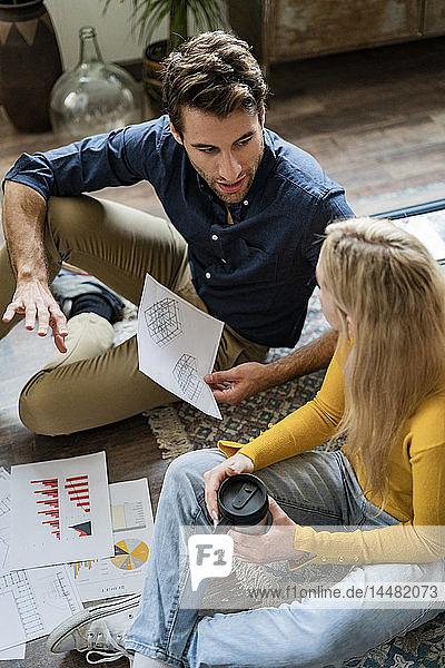 Geschäftsmann und Geschäftsfrau sitzen auf dem Boden und diskutieren Dokumente in einem Loft-Büro