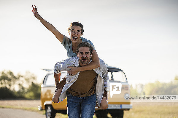 Happy couple doing a road trip with a camper  pretending to fly on the road
