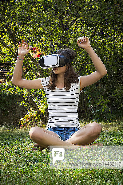 Girl sitting on meadow in the garden using Virtual Reality Glasses