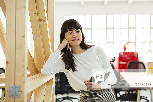 Smiling young woman with notebook in office