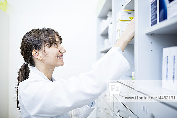 Smiling pharmacist checking medicine at cabinet in pharmacy