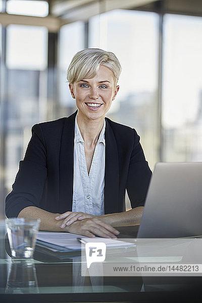 Porträt einer lächelnden Geschäftsfrau  die mit Laptop am Schreibtisch im Büro sitzt