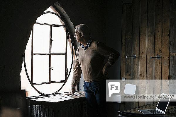 Schwerer leitender Geschäftsmann schaut im Amt aus dem Fenster