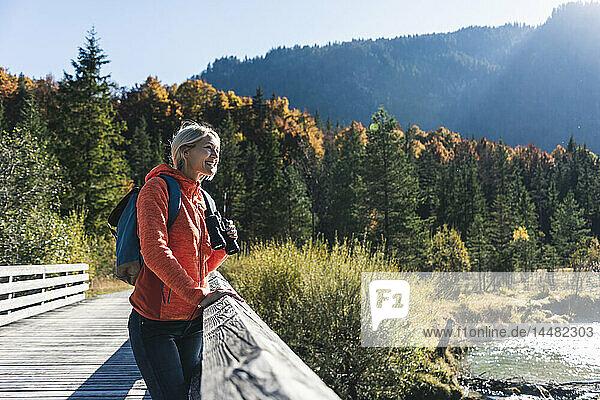 Österreich,  Alpen,  Frau auf einer Wanderung auf einer Brücke stehend mit Fernglas
