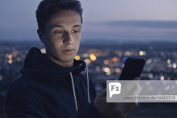 Porträt eines jungen Mannes  der sich abends ein glänzendes Smartphone ansieht