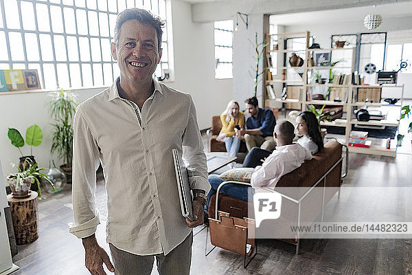 Portrait of smiling mature businessman with coworkers in background in loft office