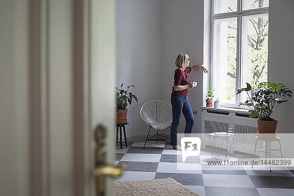 Reife Frau zu Hause  die aus dem Fenster schaut