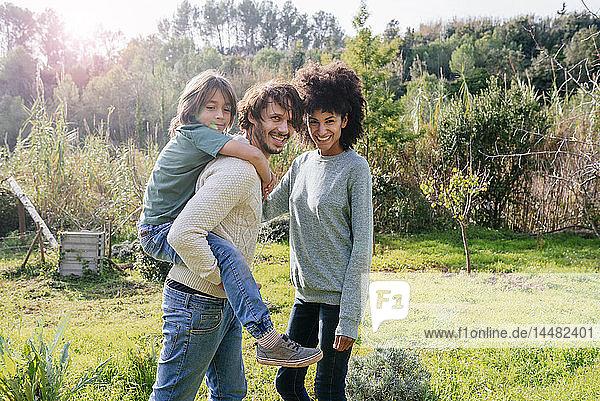 Glückliche Familie beim Spaziergang auf dem Land  Vater trägt Sohn huckepack