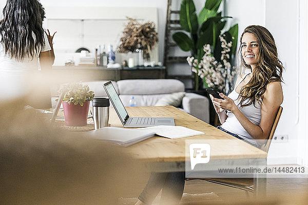 Lächelnde Frau mit Handy bei Tisch zu Hause