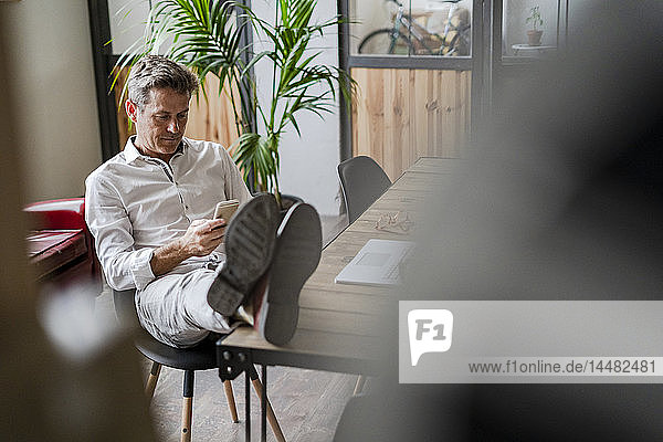 Businessman sitting with feet on desk using cell phone