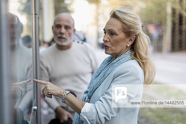 Spain  Barcelona  senior couple checking the timetable at tram stop in the city