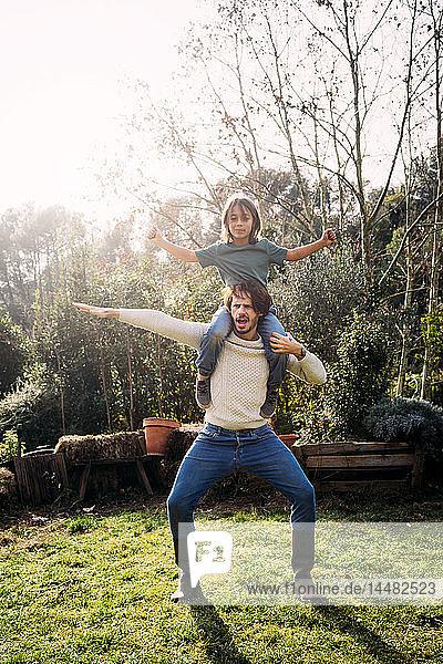 Vater spielt mit seinem Sohn und trägt ihn huckepack in einem Garten