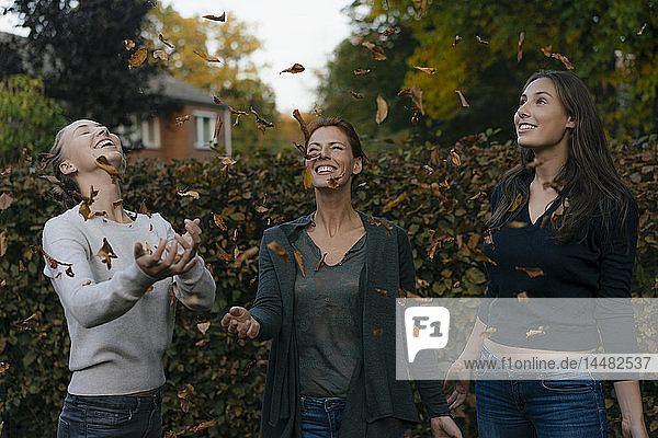 Sorglose Mutter mit zwei Teenager-Mädchen  die Herbstblätter in den Garten werfen