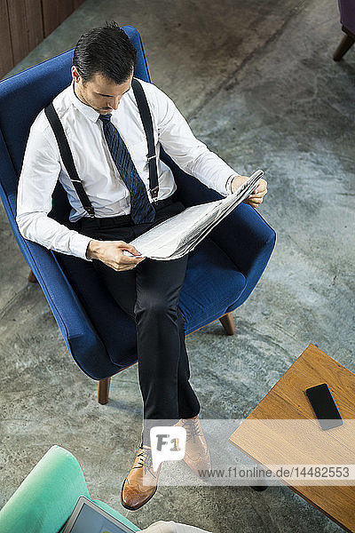 Top view of businessman sitting in blue armchair reading newspaper