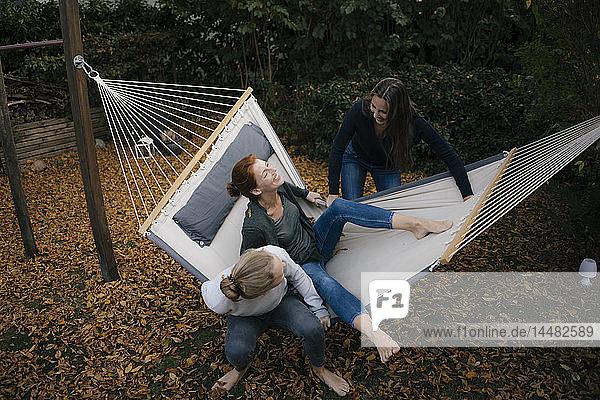 Glückliche Mutter mit zwei Teenager-Mädchen in Hängematte im Garten im Herbst