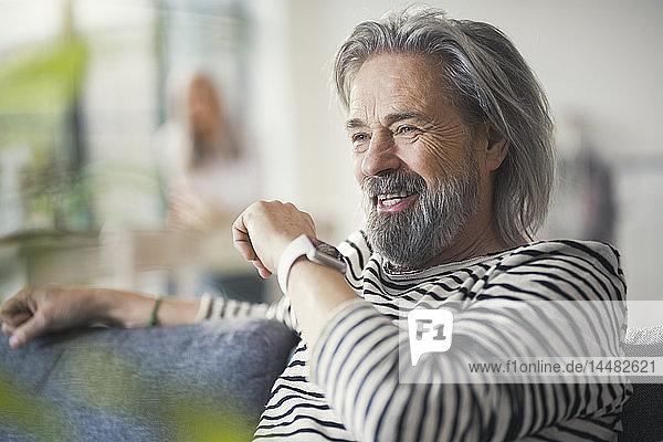 Älterer Mann sitzt auf der Couch und redet mit der Smartwatch