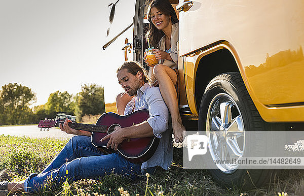 Affectionate couple on a road trip  taking a break  playing guitar