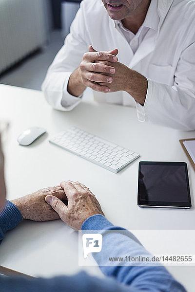 Nahaufnahme eines Arztes im Gespräch mit einem älteren Patienten in der medizinischen Praxis