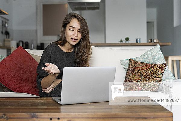 Junge Frau sitzt auf ihrer Couch und chattet auf ihrem Laptop
