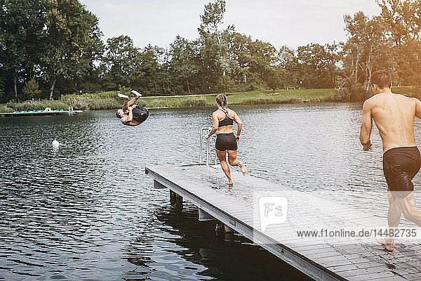 Sportive people running on jetty  jumping into lake after workout training