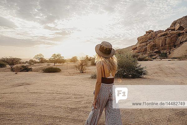 Namibia  Spitzkoppe  Rückansicht einer Frau mit Hut bei Sonnenuntergang