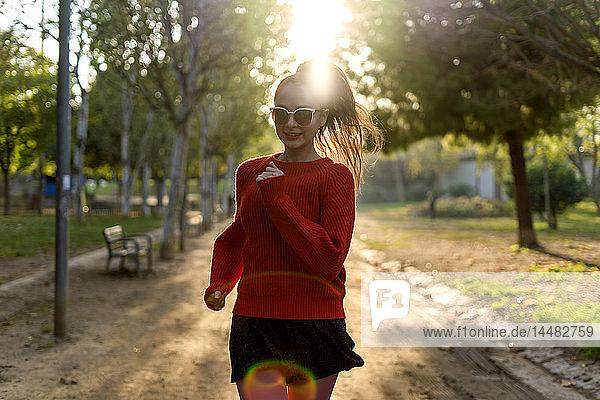 Junge Frau mit Sonnenbrille,  rennt in einem Park